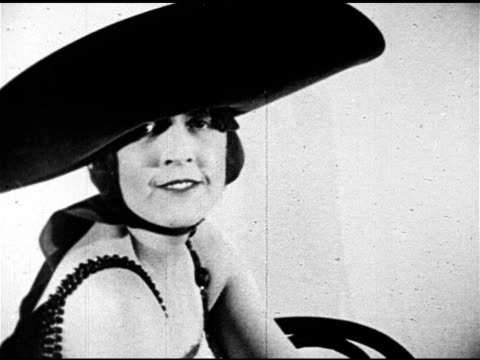 fashion hats woman w/ short hair dressed in flapper dress modeling widebrim hat seated female model w/ curly hair in ornate feather hat w/ chin strap... - chin stock videos and b-roll footage