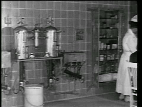 vidéos et rushes de b/w 1920s pan female nurse examining male patient in office / newsreel - 1920