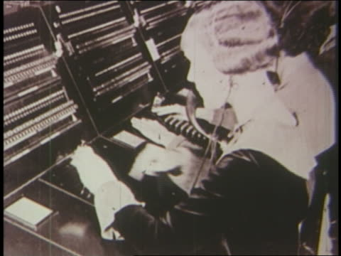 b/w 1920s female telephone operators - 電話交換機点の映像素材/bロール