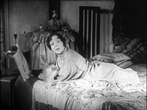 vidéos et rushes de b/w 1920s flapper lying on bed reading newspaper / friend comes + shows her toy dog / newsreel - peluche