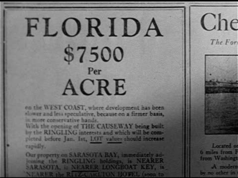 crowd of men gathered around salesman, print ad for west coast of florida land , neighborhood w/ homes partially completed, residents w/ tents,... - salesman stock videos & royalty-free footage