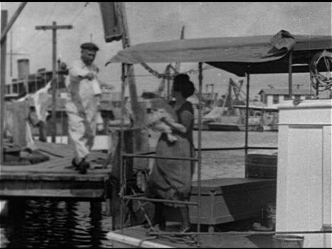 FLORIDA LAND BOOM WS Woman hanging laundry on line milkman delivering milk to woman on houseboat small boy fishing from deck SUNSET Women in...