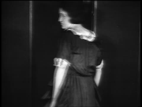 vídeos de stock, filmes e b-roll de b/w 1920s girl modeling dress in vocational school / newsreel - only teenage girls