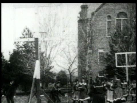 vidéos et rushes de 1920s ws girls in dresses playing basketball / united states - panier de basket