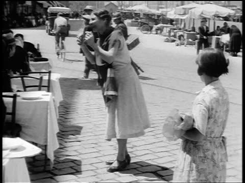 vídeos de stock e filmes b-roll de b/w 1920s gypsy woman entertaining patrons seated at outdoor restaurant / paris / documentary - café edifício de restauração