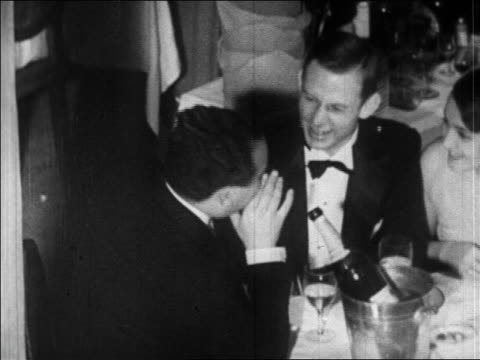 b/w 1920s high angle 2 men in tuxedos sitting at table with champagne talking + laughing / paris / newsreel - formal stock videos and b-roll footage