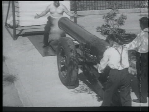 b/w 1920s high angle bare-chested man (fa/jr? richards) getting hit by cannon ball in stomach for stunt - cannon stock videos & royalty-free footage