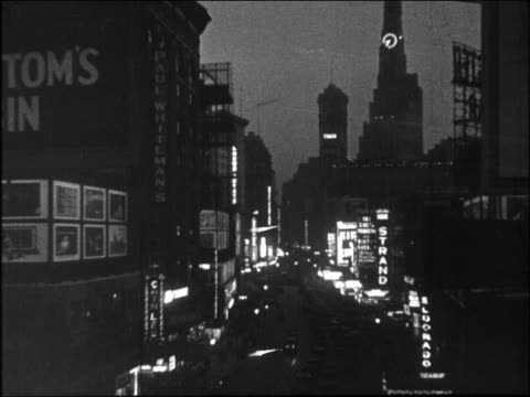 b/w 1920s high angle broadway with lights at night / new york city - broadway manhattan stock-videos und b-roll-filmmaterial