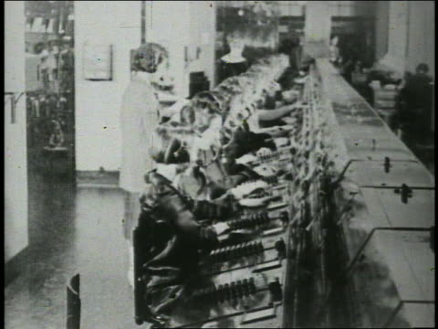 b/w 1920s high angle busy telephone operators working at switchboard - 電話交換機点の映像素材/bロール