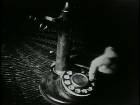 vidéos et rushes de b/w 1920s high angle close up hand of person dialing on telephone - 1920