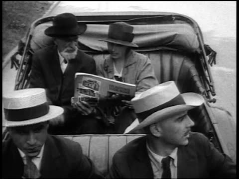 b/w 1920s high angle four people sitting in convertible / man + woman in backseat with magazine / newsreel - magazine publication stock videos & royalty-free footage