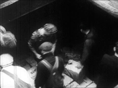 b/w 1920s high angle men in overalls moving boxes on ship smuggling bootleg liquor / prohibition / newsreel - 密輸点の映像素材/bロール