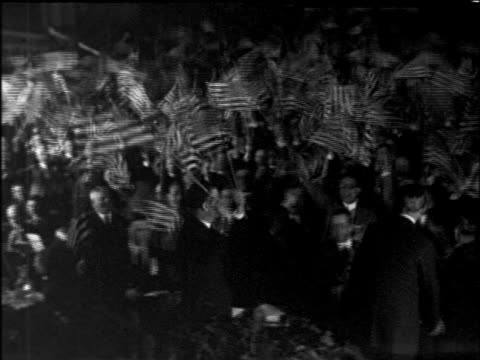 b/w 1920s high angle pan men waving american flags / industrial - political rally stock videos & royalty-free footage