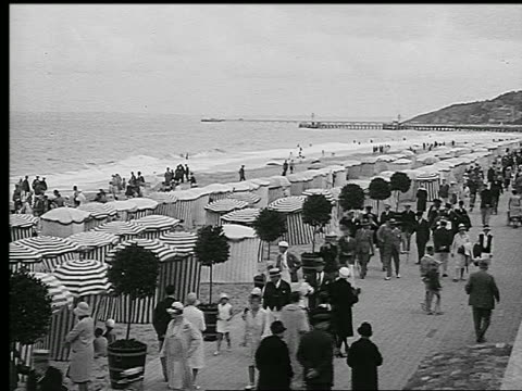 b/w 1920s high angle rows of umbrellas + crowd of people walking + swimming on beach / deauville, france - parasol stock videos & royalty-free footage