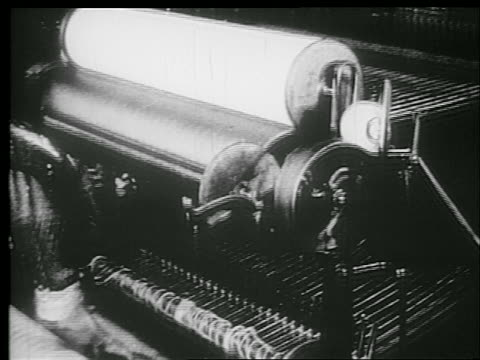 b/w 1920s high angle tilt down man working on mechanical loom in textile factory - webstuhl stock-videos und b-roll-filmmaterial