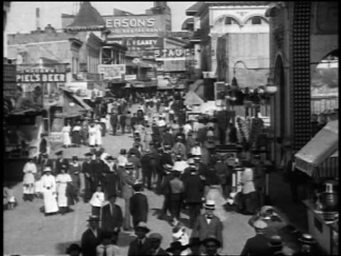 b/w 1920s high angle time lapse people walking by buildings at coney island / nyc / newsreel - coney island brooklyn stock videos & royalty-free footage