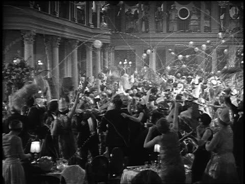 B/W 1920s high angle wide shot crowd of people in party hats throwing streamers, blowing horns in ballroom