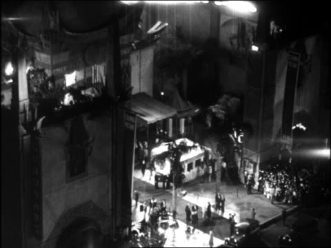 vídeos de stock, filmes e b-roll de b/w 1920s high angle wide shot searchlights crowd gathered at graumann's chinese theater for movie premiere - estreia