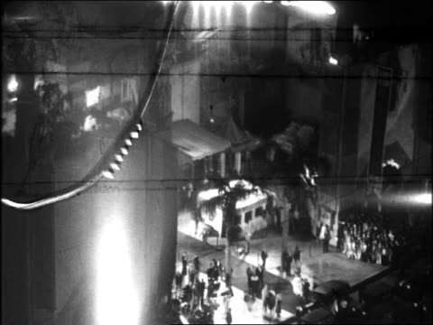 B/W 1920s high angle wide shot searchlights crowd gathered at Graumann's Chinese Theater for movie premiere