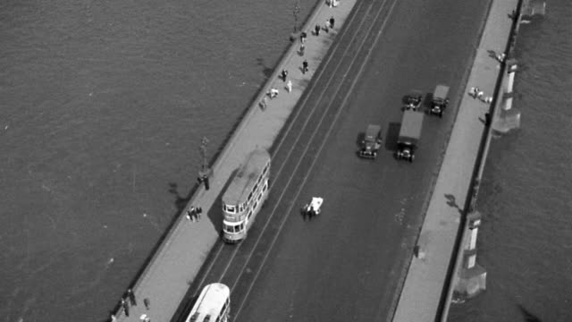 b/w 1920s high angle wide shot tilt up from bridge with traffic over thames river to cityscape / london, england - tram stock videos & royalty-free footage