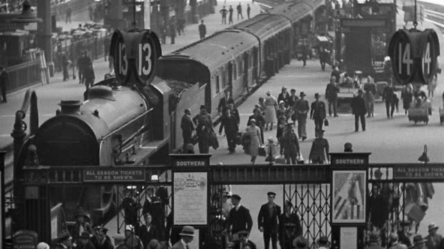 B/W 1920s high angle wide shot train station with passengers walking on platform / London, England