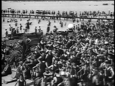 vídeos y material grabado en eventos de stock de b/w 1920s pan huge crowd on beach waving to camera / documentary - traje de baño de una pieza