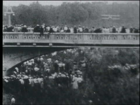 vidéos et rushes de b/w 1920s pan huge crowd on bridge watches as biplane flies underneath bridge - exploit sportif