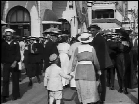 b/w 1920s iris in people walking by buildings on street at coney island / nyc / newsreel - coney island brooklyn stock videos & royalty-free footage