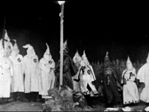 vídeos de stock, filmes e b-roll de ku klux klan kkk klansmen in hooded robes standing next to burning cross klansmen walking in line white supremacists supremacy racists racism - ku klux klan
