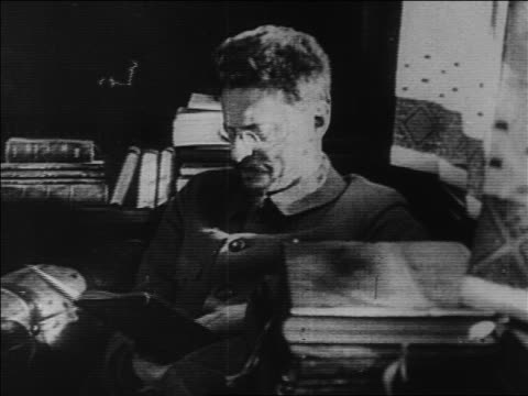 stockvideo's en b-roll-footage met 1920s leo trotsky sitting surrounded by books / starts talking / russia / documentary - alleen één oudere man
