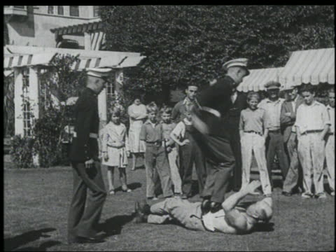 B/W 1920s line of men jumping on stomach of FA/JR? Richards / crowd of men + boys watches in background
