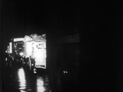 vidéos et rushes de b/w 1920s line of trucks loaded with barrels of bootleg liquor at night / prohibition / newsreel - véhicule utilitaire léger