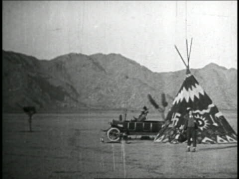 b/w 1920s long car emerging from teepee in valley / feature - nazi swastika stock videos & royalty-free footage
