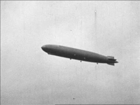 B/W 1920s low angle Graf Zeppelin flying in sky