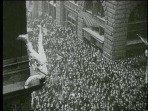 b/w 1920s man balancing on his head on ledge of city building as crowd below watches - stunt person stock videos & royalty-free footage