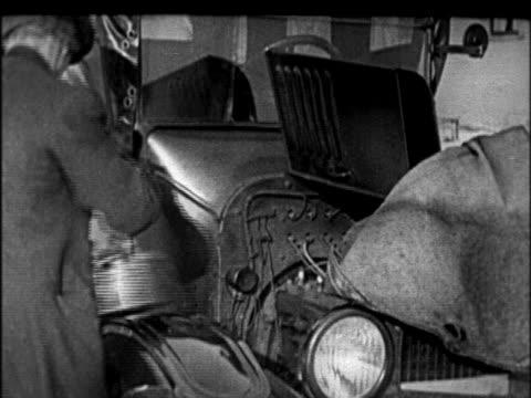 vidéos et rushes de b/w 1920s man closing hood of model t car in winter / newsreel - ford model t