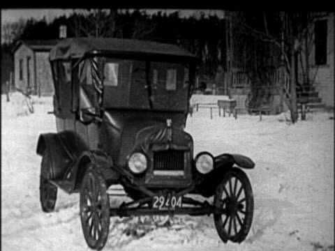 b/w 1920s man cranking engine of model t car in winter + driving off / newsreel - model t stock videos and b-roll footage