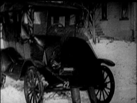 vidéos et rushes de b/w 1920s man cranking model t car in sub-zero temperatures / newsreel - ford model t