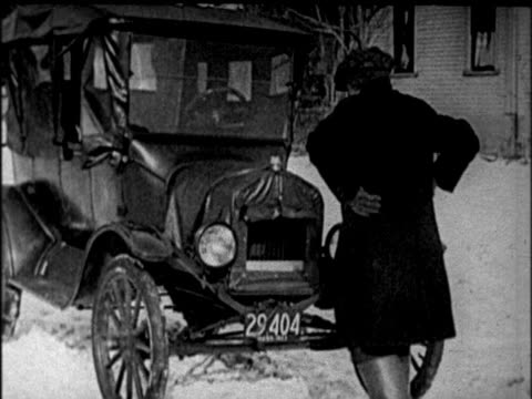 b/w 1920s man cranking model t car in sub-zero temperatures / newsreel - model t stock videos and b-roll footage