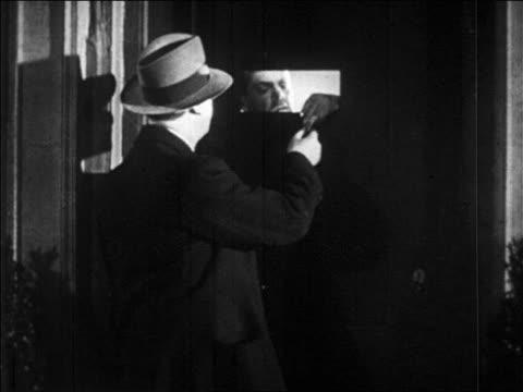 b/w 1920s man handing something thru doorslot of speakeasy enters / prohibition / newsreel - 禁酒法点の映像素材/bロール