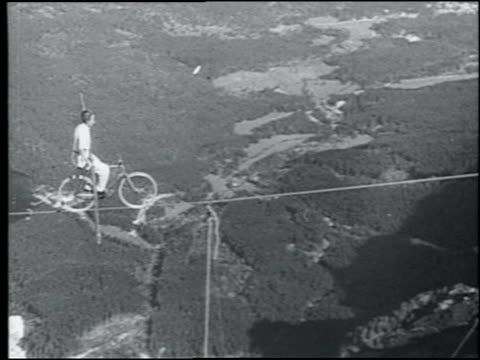 b/w 1920s pan man holding pole riding on bicycle on tightrope above alps - risk stock videos & royalty-free footage