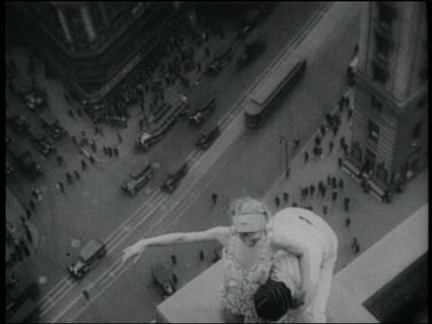 vídeos y material grabado en eventos de stock de b/w 1920s man holding woman in air on ledge of paramount building / traffic on broadway below / nyc - paramount building