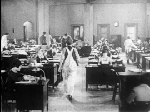 1920s man in overalls walking past rows of women working at desks / newsreel - フリーアドレス点の映像素材/bロール