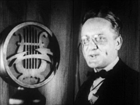 vidéos et rushes de b/w 1920s man in pince nez talking into microphone in radio studio - un seul homme d'âge moyen
