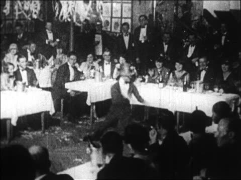 B/W 1920s man in top hat doing exuberant dance in floorshow / Paris, France / documentary