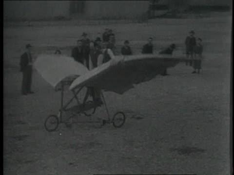 vídeos de stock, filmes e b-roll de 1920s ws man pedaling experimental plane with flapping wings  - experimento