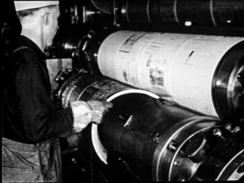 b/w 1920s man placing plates on round printing press in newspaper printing plant / newsreel - nachrichtenredaktion stock-videos und b-roll-filmmaterial