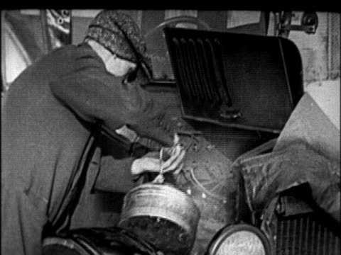 b/w 1920s man pouring hot water from kettle over engine of model t car in winter / newsreel - フォード・t型モデル点の映像素材/bロール