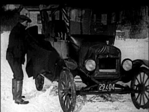 b/w 1920s man removing coat + cranking engine of model t car in winter / newsreel - model t stock videos and b-roll footage