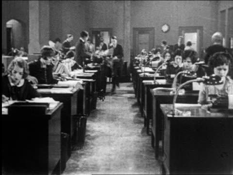 B/W 1920s man roller skating past rows of women working at desks / newsreel